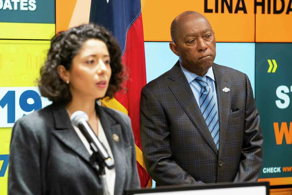 "Houston Mayor Sylvester Turner listens as Harris County Judge Lina Hidalgo speaks during a press conference announcing that the county will adopt a ""Stay Home, Work Safe"" strategy until April 3, Tuesday, March 24, 2020, at TranStar in Houston."
