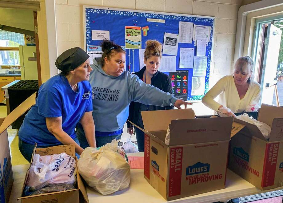 From left, Janet Eslick, Mandy Lattimer, Sara Hegel and Ginny Tigner package food and supplies that will be delivered to the families of Coleman Community Schools students Tuesday, March 17 at Community of Christ Church in Sanford. (Mitchell Kukulka/mitchell.kukulka@mdn.net)