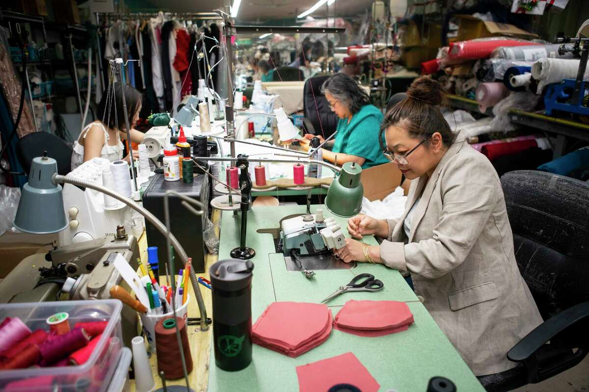 Designer Chloe Dao, rights, threads a machine as she works to make surgical masks in her workspace in the Heights, Monday, March 23, 2020, in Houston. Dao temporarily closed her 20-year-old namesake boutique last week and is now making surgical masks and giving them away free to healthcare workers.