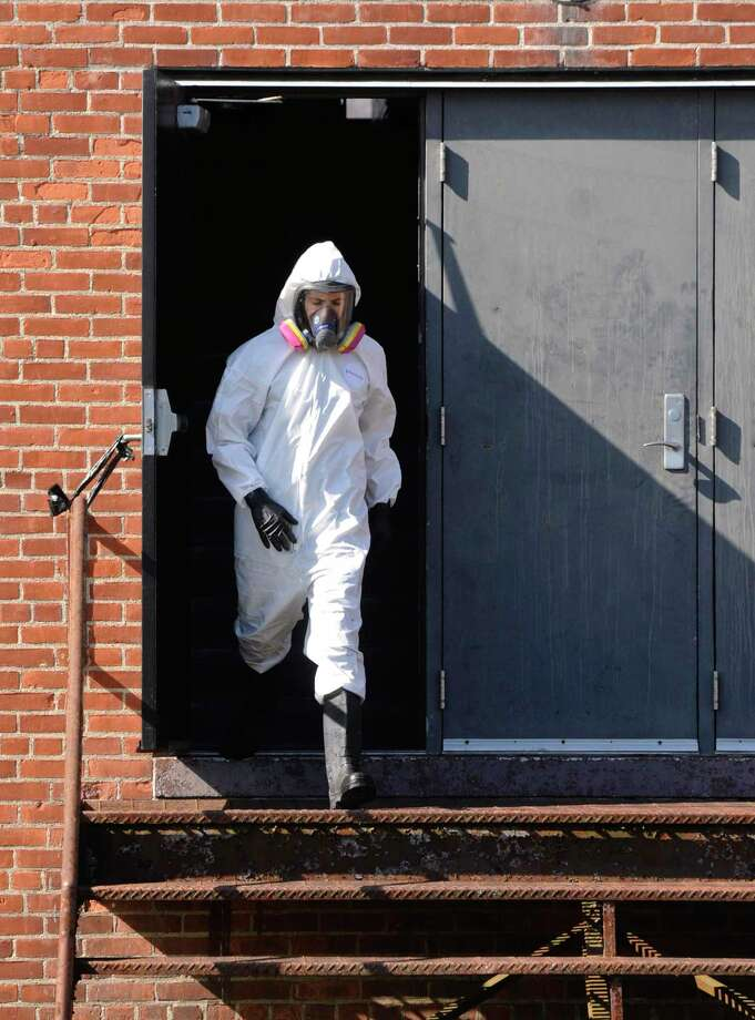 A worker comes out of the War Memorial as the city was cleaning and converting the building in Rogers Park into temporary housing for the homeless. Tuesday, March 24, 2020, in Danbury, Conn. Photo: H John Voorhees III / Hearst Connecticut Media / The News-Times