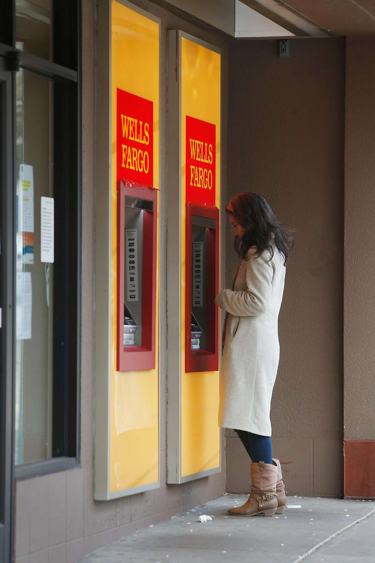 Dana DeLara of San Francisco uses an ATM at a temporarily closed Wells Fargo branch due to the coronavirus shelter in place on 24th Street on Tuesday, March 24, 2020 in San Francisco, Calif.