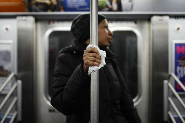 A New York City subway rider protects her hand with a tissue as she holds onto a pole as COVID-19 concerns shrink ridership.