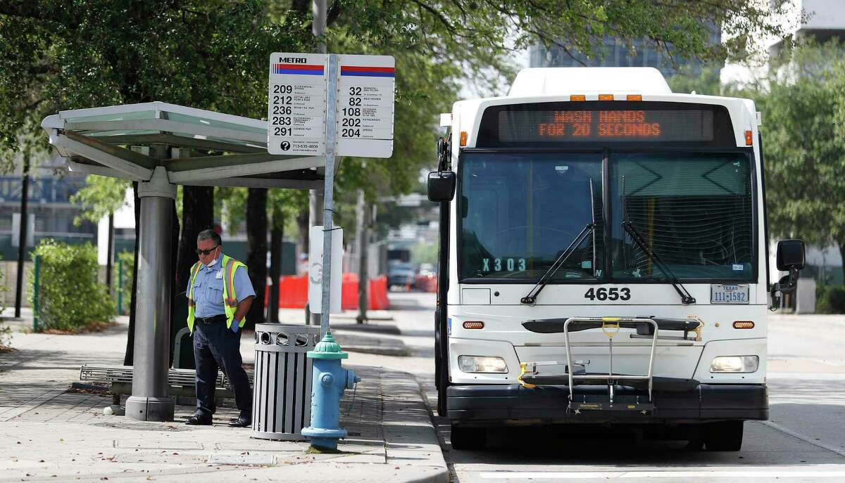 """A Metropolitan Transit Authority bus driver takes a break next to his bus which was broadcasting signs such as """"Wash Hands for 20 Seconds"""" in downtown Houston on March 24, 2020."""