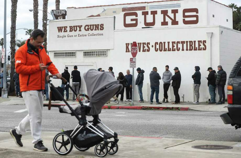 >> What exactly is an essential business?  A man walks with a stroller as people stand in line outside the Martin B. Retting, Inc. guns store on March 15, 2020 in Culver City, Calif. The spread of Coronavirus (COVID-19) has prompted some Americans to line up for supplies in a variety of stores. Photo: Mario Tama / Getty Images / 2020 Getty Images