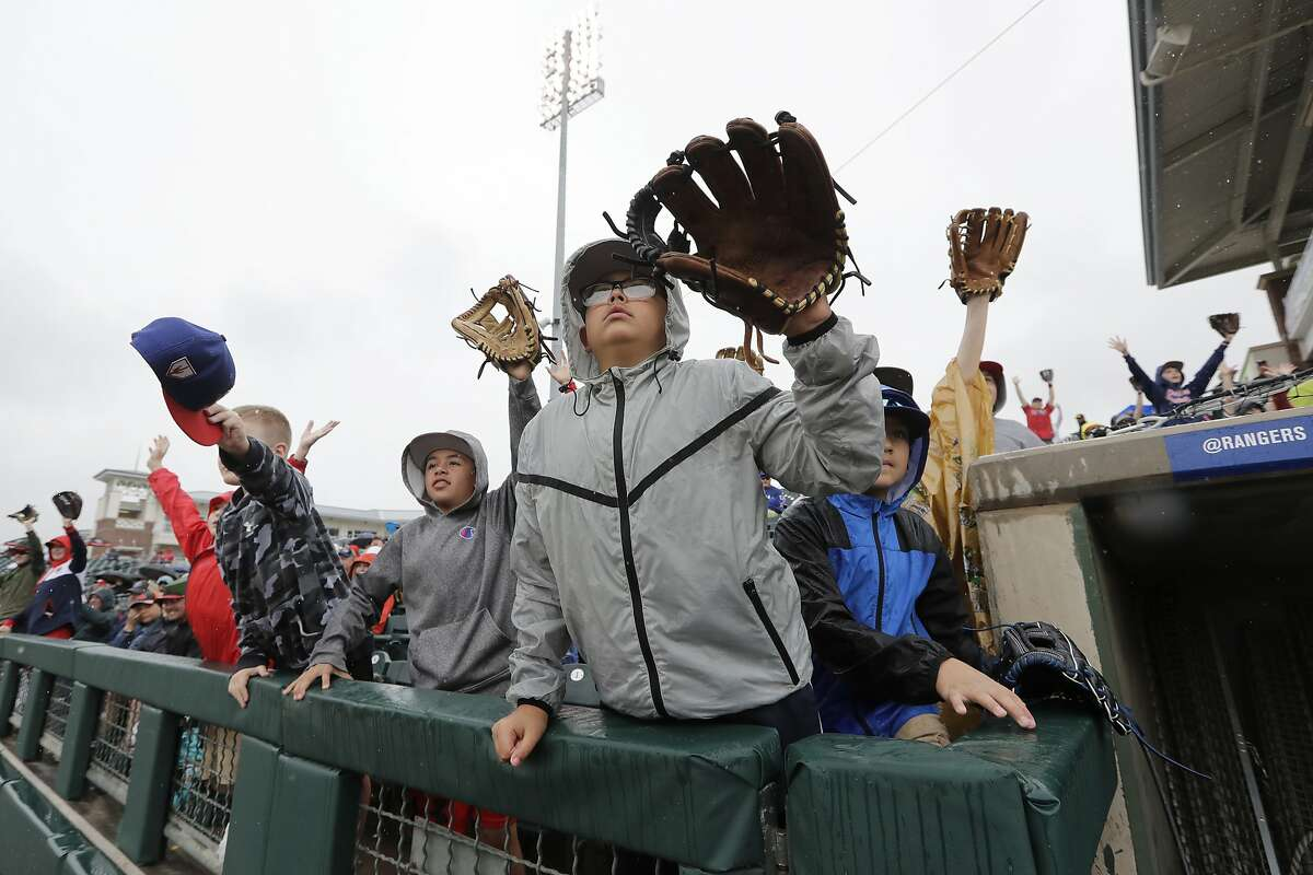 Children call for a ball to be tossed their way between innings of a spring training baseball game between the San Francisco Giants and the Texas Rangers on Wednesday, March 11, 2020, in Surprise, Ariz. (AP Photo/Elaine Thompson)