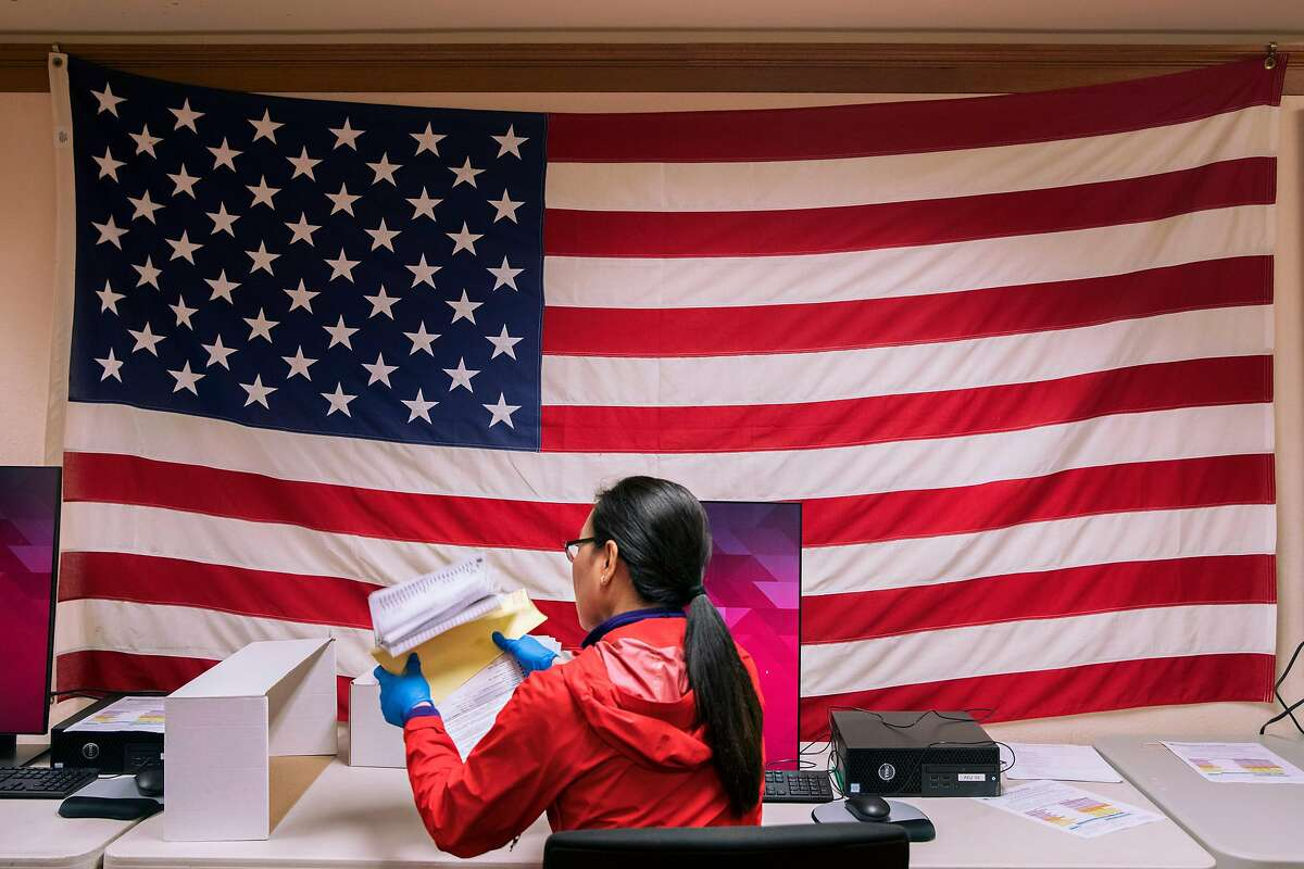 An election worker sits in front of a large American flag while entering faxed-in ballots ahead of the March 3rd election at San Francisco City Hall in San Francisco, Calif. Friday, February 28, 2020.