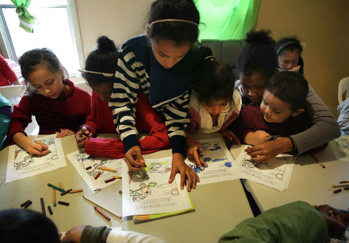 South Texas groups are trying to help immigrant families amid the coronavirus outbreak. Migrant children crowd around a table to color pictures provided by Miriam Maus, a youth pastor in Nuevo Laredo, at the Good Samaritan Shelter in the same city on Wednesday, Nov. 13, 2019.