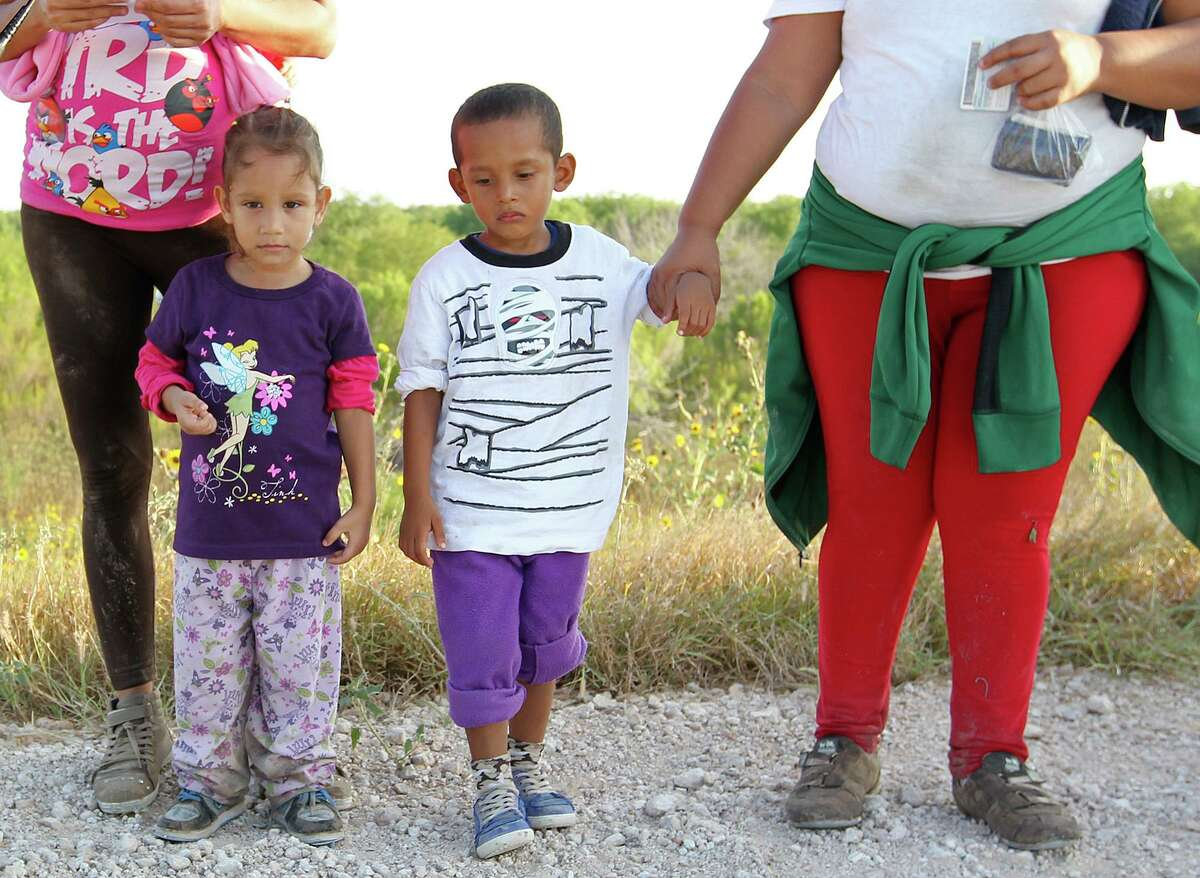 Migrant children living in close quarters may be at risk of contracting the novel coronavirus. The children are put in federal shelters across the country after crossing the U.S.-Mexico border. Here, migrant children stand by adults as a U.S. Border Patrol agent questions them near Anzalduas Park, southwest of McAllen, Texas, Wednesday, June 11, 2014.