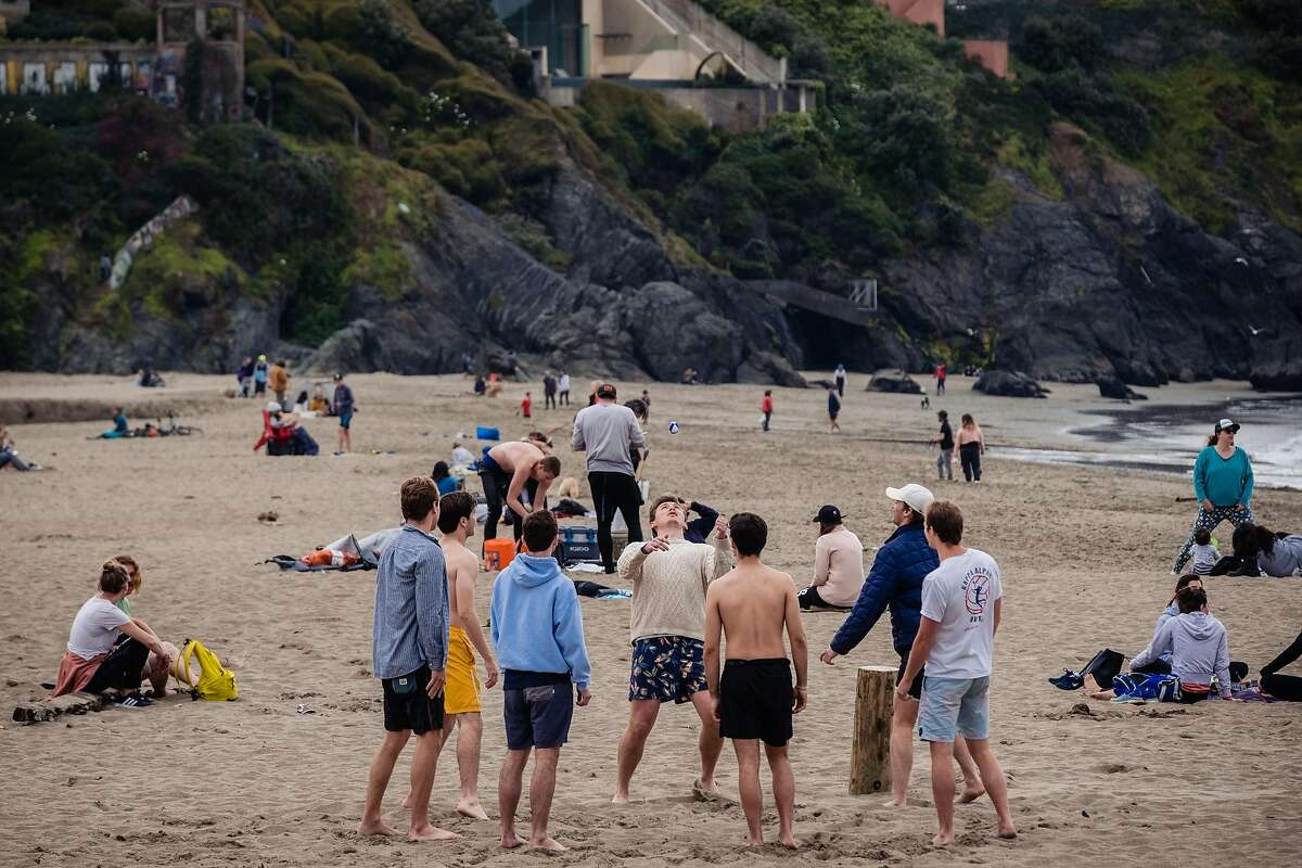 Some people play wacky sack on a crowded Baker Beach on this the 5th day of the city wide shelter in place order in San Francisco, Calif. on Saturday, March 21, 2020.