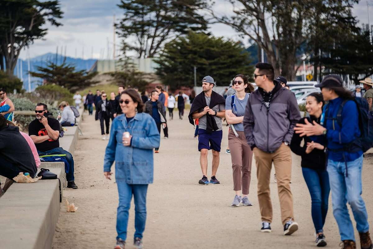 People are seen walking and jogging at Chrissy Field on this the 5th day of the city wide shelter in place order in San Francisco, Calif. on Saturday, March 21, 2020.