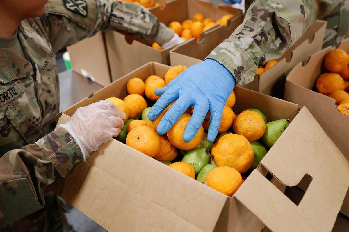 Members of the National Guard pack boxes of produce at Second Harvest of Silicon Valley Tuesday, March 24, 2020, in San Jose, Calif.