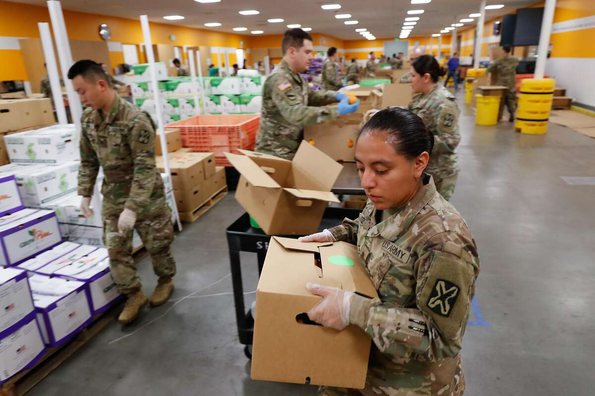 Kimberly Ortiz, of Los Angeles, carries a box of fruit to be stacked on a pallet as members of the National Guard pack boxes of produce at Second Harvest of Silicon Valley Tuesday, March 24, 2020, in San Jose, Calif.