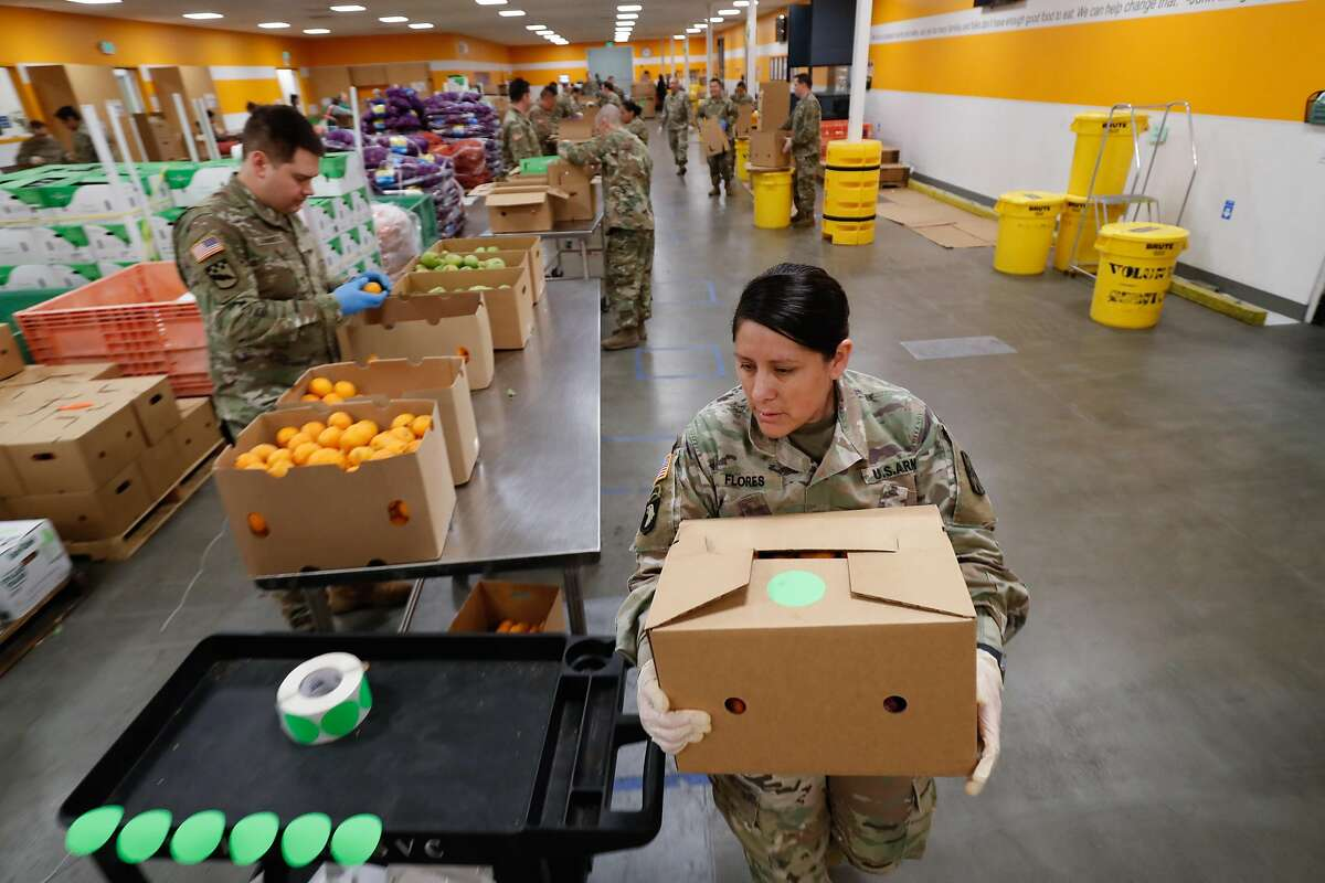 Gabriella Flores, of Sacramento, carries a box of fruit to be stacked on a pallet as members of the National Guard pack boxes of produce at Second Harvest of Silicon Valley Tuesday, March 24, 2020, in San Jose, Calif.