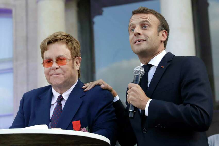 French President Emmanuel Macron, right, and Sir Elton John address the crowd in the courtyard of the presidential Elysee Palace in Paris, Friday, June 21, 2019. Sir Elton John received the Legion of Honor, France's highest award, during a visit to the presidential Elysee Palace (AP Photo/Lewis Joly, Pool)