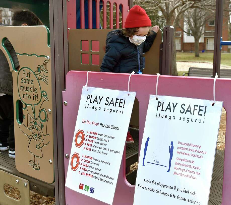 A young child with a protective face mask plays on the Jocelyn Square park playground on the corner of Humphrey Street and East Street in New Haven Tuesday in the proximity of a sign that provides details of social distancing during the coronavirus pandemic. Photo: Peter Hvizdak / Hearst Connecticut Media / New Haven Register