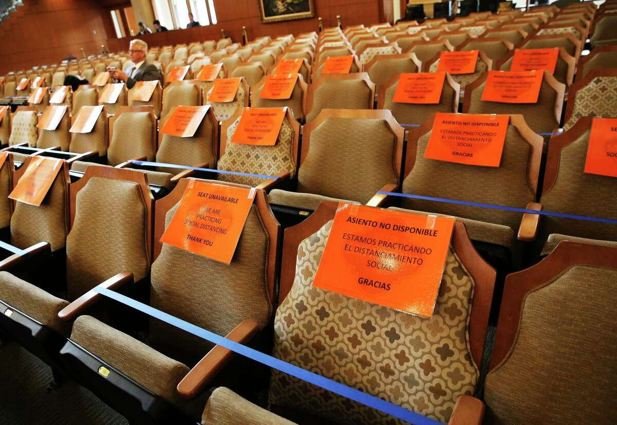 Signage is placed on chairs to observe social distancing during a meeting by Mayor Ron Nirenberg and the City Council as they discuss extending the latest Coronavirus emergency declaration to 30 days on Thursday, Mar. 19, 2020. Two council members: District 8's Manny Peláez and District 3's Rebecca J. Viagran were present via video-conferencing since both are self-quarantining from their homes. The meeting was held under attendance restriction on no more than 50 people and seating in the room observed social distancing with signage included.