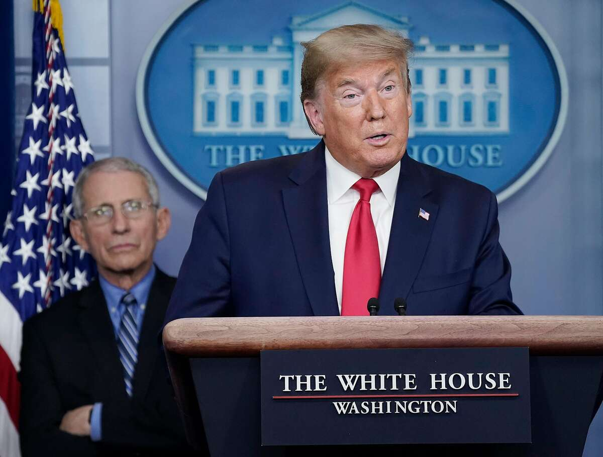 Dr. Anthony Fauci (L), director of the National Institute of Allergy and Infectious Diseases, listens to U.S. President Donald Trump speak during a briefing on the coronavirus pandemic, in the press briefing room of the White House.