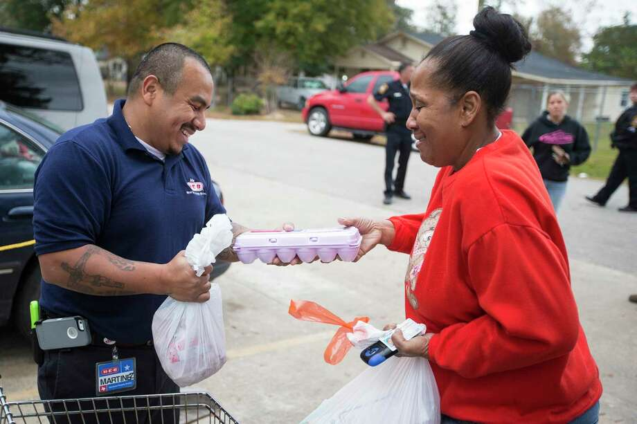 "Officials with the Montgomery County Food Bank and the YMCA are teaming up as usual to help those in need. This time it is a food give-away from the ""mobile market"" scheduled for 10 a.m. to noon on Saturday, March 28, at the Shadowbend YMCA in The Woodlands. The first 150 families will receive for free more than 70 pounds of different foods on a first-come, first-serve basis. In this Villager archicve photograph frm 2013, H-E-B employee Daniel Martinez helps Marcella Charles gather her food as Operation Refuge gives away food and toys on Dec. 19, 2013, at the food pantry in Cleveland. Photo: ANDREW BUCKLEY / The Advocate / The Advocate"