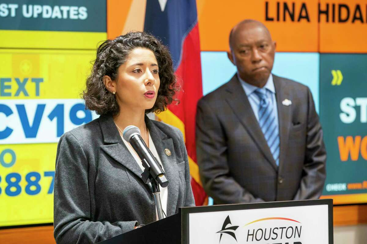 """Harris County Judge Lina Hidalgo speaks as Mayor Sylvester Turner listens during a press conference announcing that the county will adopt a """"Stay Home, Work Safe"""" strategy until April 3, Tuesday, March 24, 2020, at TranStar in Houston."""