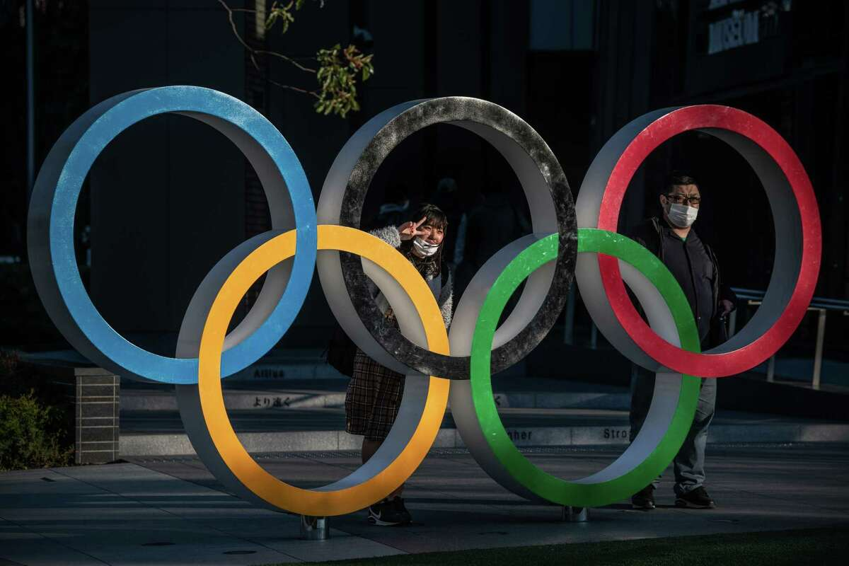 TOKYO, JAPAN - MARCH 24: People wearing face masks pose for photographs next to Olympic Rings on March 24, 2020 in Tokyo, Japan. Although an official decision is yet to be announced, International Olympic Committee member Dick Pound has said the Tokyo 2020 Olympic Games will be postponed by one year because of the Covid-19 coronavirus after the chairman of the British Olympic Association said Great Britain would be unlikely to send a team to Tokyo this summer while Australia and Canada also said they will not compete as the global Covid-19 coronavirus pandemic that has so far seen over 380,000 infections around the world forces countries to take drastic measures to protect their populations. (Photo by Carl Court/Getty Images) *** BESTPIX ***