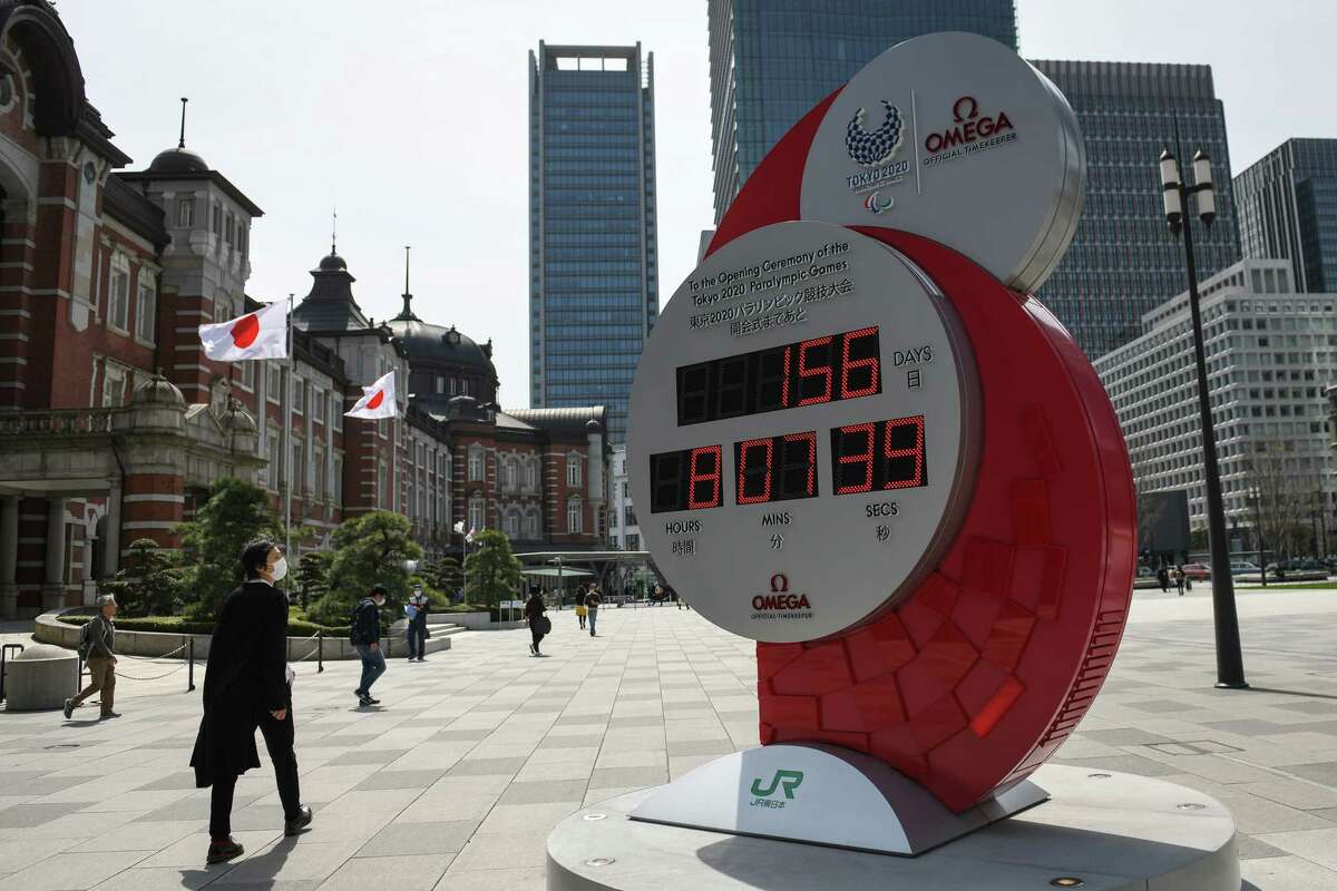 A man wearing a face mask glances at a digital clock counting down to the start of the Olympic Games in Tokyo on Sunday, March 22, 2020. For days, athletes had been voicing concerns about the 2020 Tokyo Games, worrying that they were jeopardizing their health and the health of others if they continued training while many of their countries were locked down and restricting activity because of the coronavirus pandemic. (Noriko Hayashi/The New York Times)