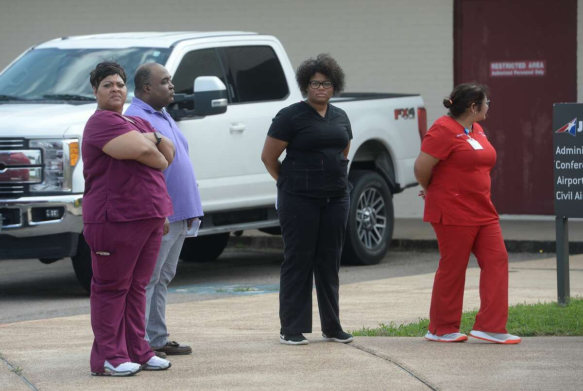 Medical personnel gather with officals as representatives from multiple Southeast Texas counties annnounce the opening of a drive-thru testing unit for COVID-19 at Jack Brooks Regional Airport Monday. Photo taken Monday, March 23, 2020 Kim Brent/The Enterprise