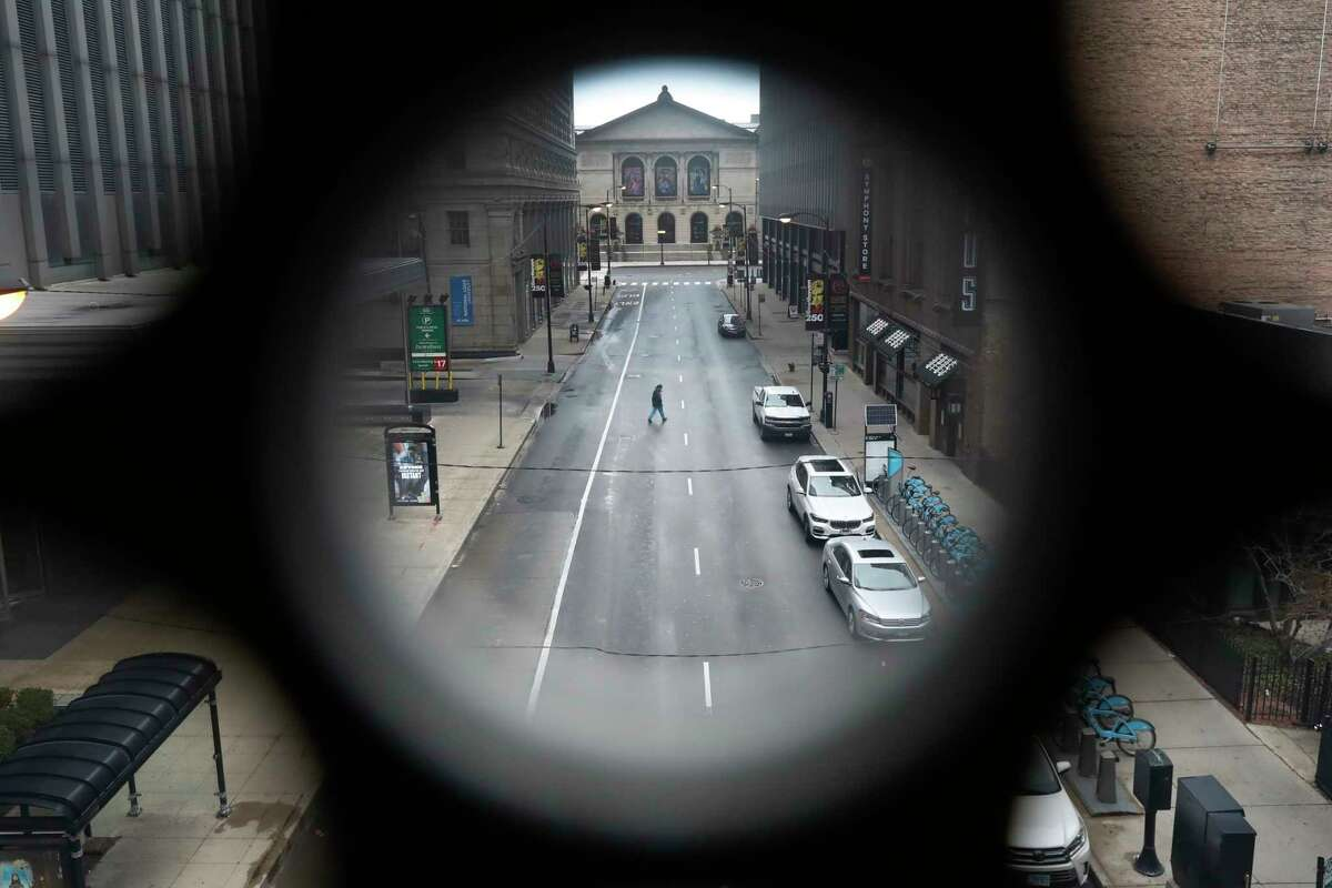FILE - In this March 23, 2020 file photo, a man walks across a nearly empty Adams Street near The Art Institute of Chicago, in Chicago, on the first work day since Illinois Gov. J.B. Pritzker gave a shelter in place order last week. As families across the country and the globe hunker down at home, there's another danger, also insidious if less immediately obvious, that worries advocates and officials: A potential spike in domestic violence. (AP Photo/Charles Rex Arbogast, File)