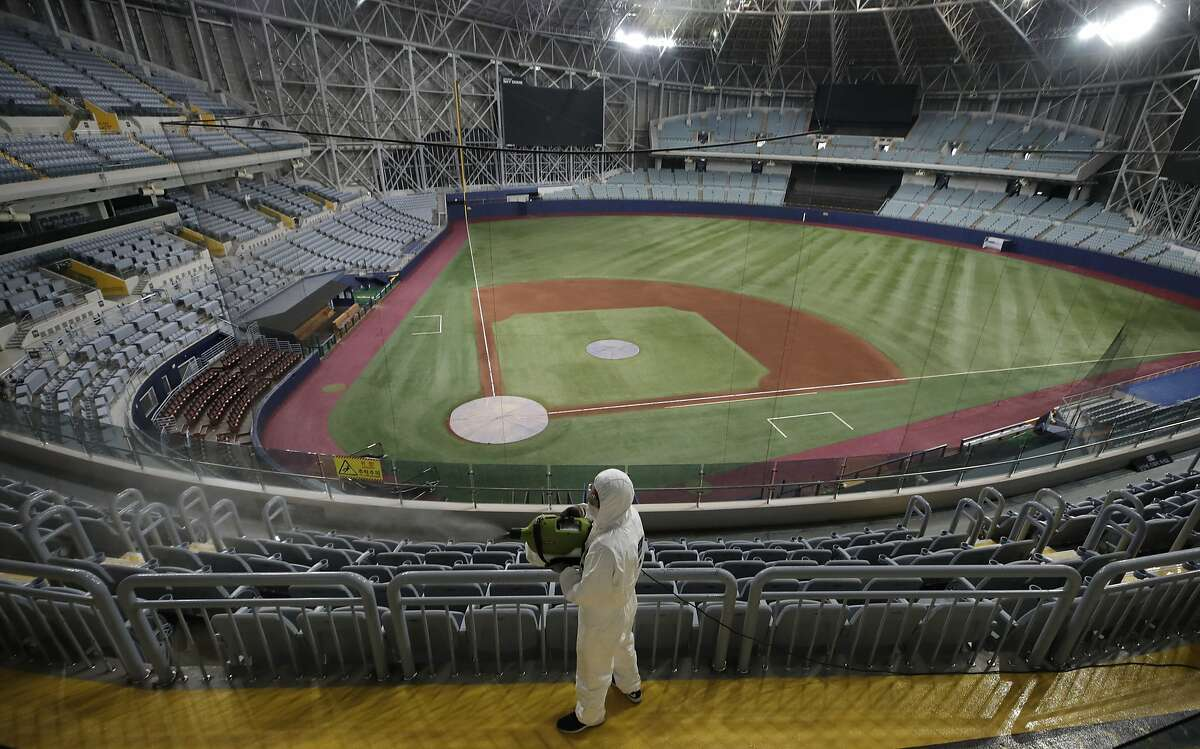 A worker wearing protective gears disinfects as a precaution against the new coronavirus at Gocheok Sky Dome in Seoul, South Korea, Tuesday, March 17, 2020. The Korea Baseball Organization has postponed the start of new season to prevent the spread of the new coronavirus. For most people, the new coronavirus causes only mild or moderate symptoms. For some it can cause more severe illness. (AP Photo/Lee Jin-man)