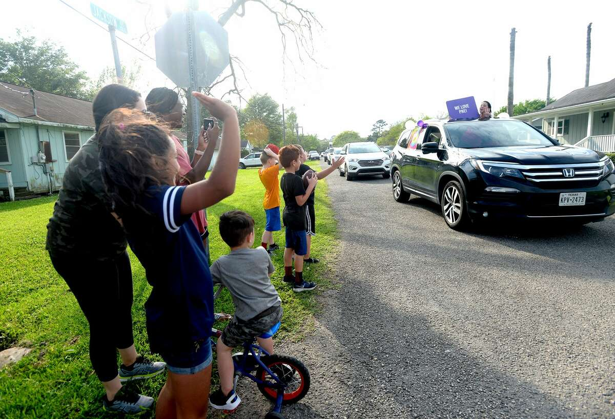 Families gather outside to wave as Port Neches Elementary School teachers parade through the city waving to students and their families who gathered outside their homes to greet them. Principal Kim Carter organized Tuesday's parade after seeing a similar event on social media. Teachers, their children and the Indian Spirit rode in cars decorated with signs, and one with a gigantic teddy bear popping up through the top of a Jeep. Photo taken Tuesday, March 24, 2020 Kim Brent/The Enterprise