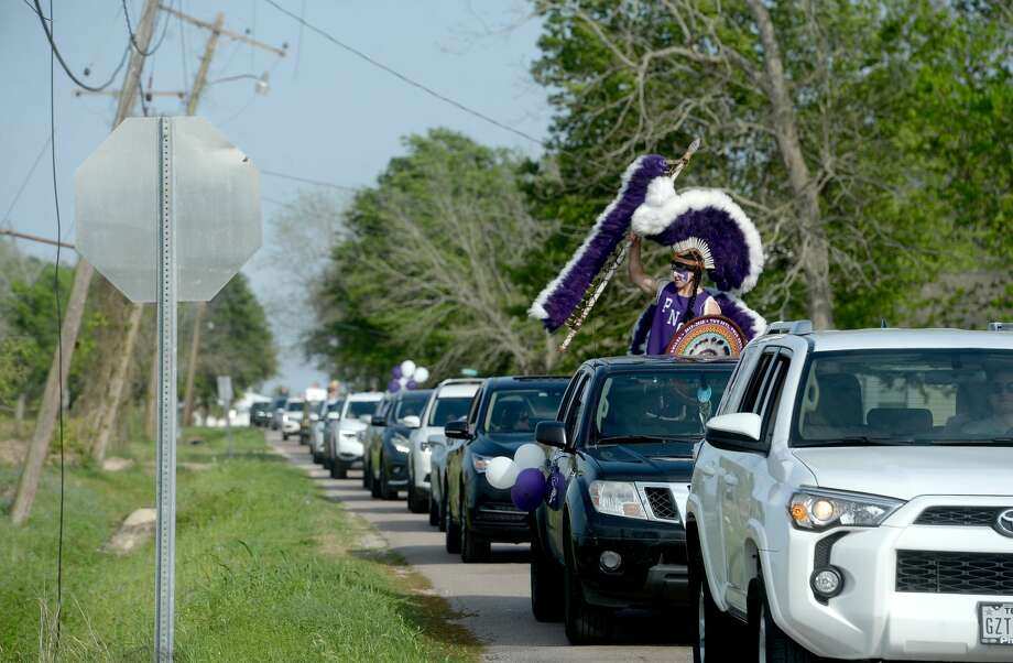 The Indian Spirit cheers as Port Neches Elementary School teachers parade through the city waving to students and their families who gathered on lawns and curbs to greet them. Principal Kim Carter organized Tuesday's parade after seeing a similar event on social media. Teachers, their children and the Indian Spirit rode in cars decorated with signs, and one with a gigantic teddy bear popping up through the top of a Jeep. Photo taken Tuesday, March 24, 2020 Kim Brent/The Enterprise Photo: Kim Brent/The Enterprise