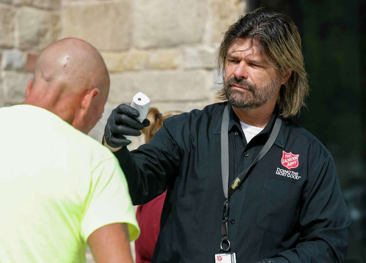 David Jenett, shelter director for the Salvation Army, checks a man's temperature before entering the Salvation Army Wayne Bergstrom Center of Hope, Thursday, March 19, 2020, in Conroe. The local Salvation Army added precautionary measures such as temperature checks and hand sanitation to those seeking shelter for the evening. The shelter's occupancy was reduced to 40 due to the coronavirus pandemic.