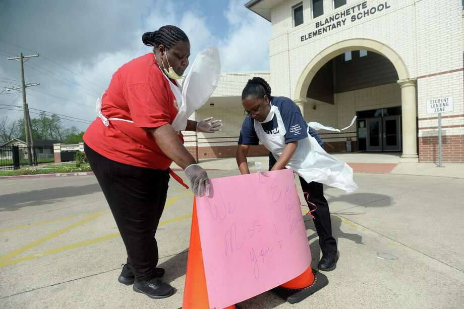 Geneva Savoy and Shavonne Durginn reattach a sign bearing a message to students as they distribute meals with other BISD cafeteria workers at Blanchette Elementary School Tuesday, the first day of food distribution for Beaumont children.    Photo taken Tuesday, March 24, 2020 Kim Brent/The Enterprise Photo: Kim Brent / The Enterprise / BEN