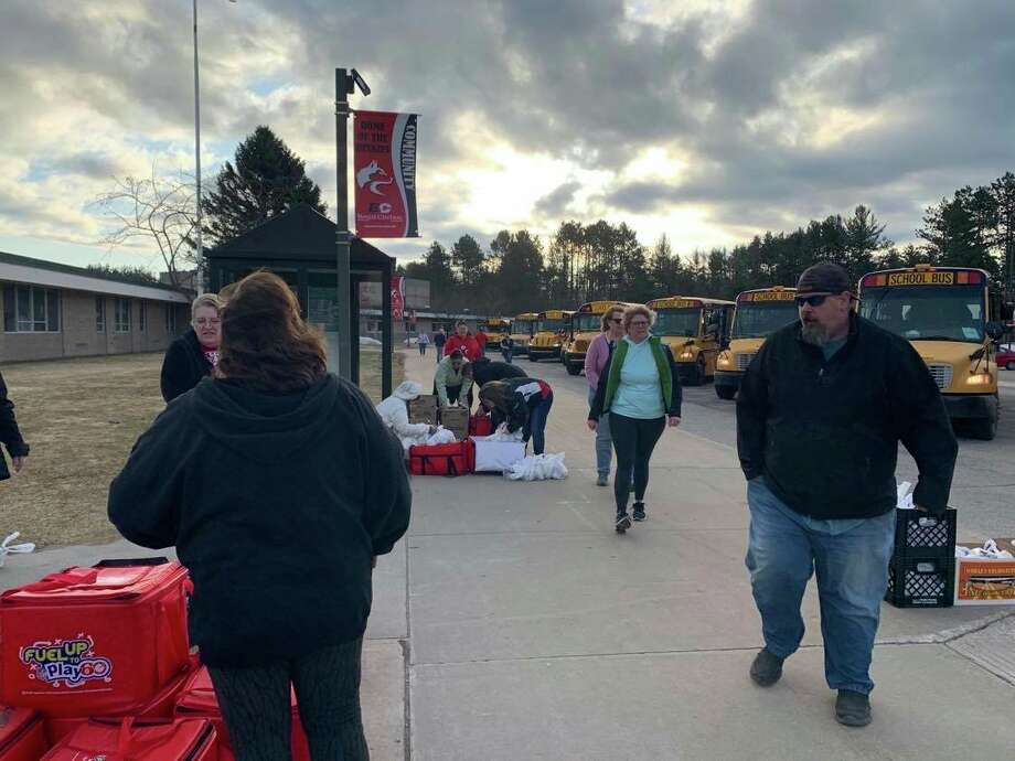Volunteers help load up buses to transport meals to children across the Benzie Central School District on March 17. (Submitted photo)