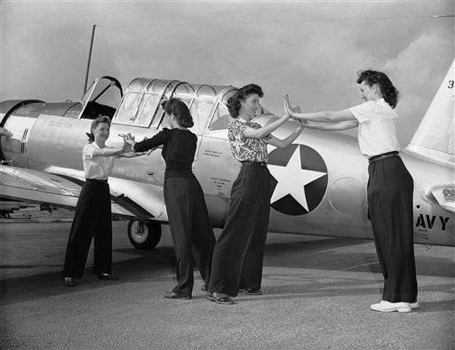 Women war workers suffer muscular aches until they become accustomed to unfamiliar tasks, so Vultee Aircraft, Inc., the first airframe plant to employ women on a large scale, instructs beginners in conditioning unused muscles for jobs building trainer planes for the Army and Navy. Common feminine complaints that Vultee seeks to correct are backache, headache and leg and ankle fatigue. A group does hand-spreading exercises in Los Angeles, March 25, 1943. (AP Photo)