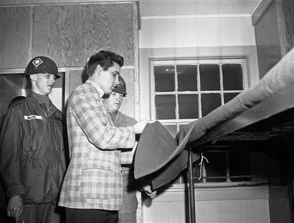 Under the watchful gaze of an instructor, Corporal John D. Smith, rock 'n' roll singer Elvis Presley adjusts a blanket on an upper bunk in Fort Chaffee, Arkansas on March 25, 1958. Presley and 21 other recruits arrived from the Memphis, Tennessee induction center. (AP Photo/William P. Straeter)