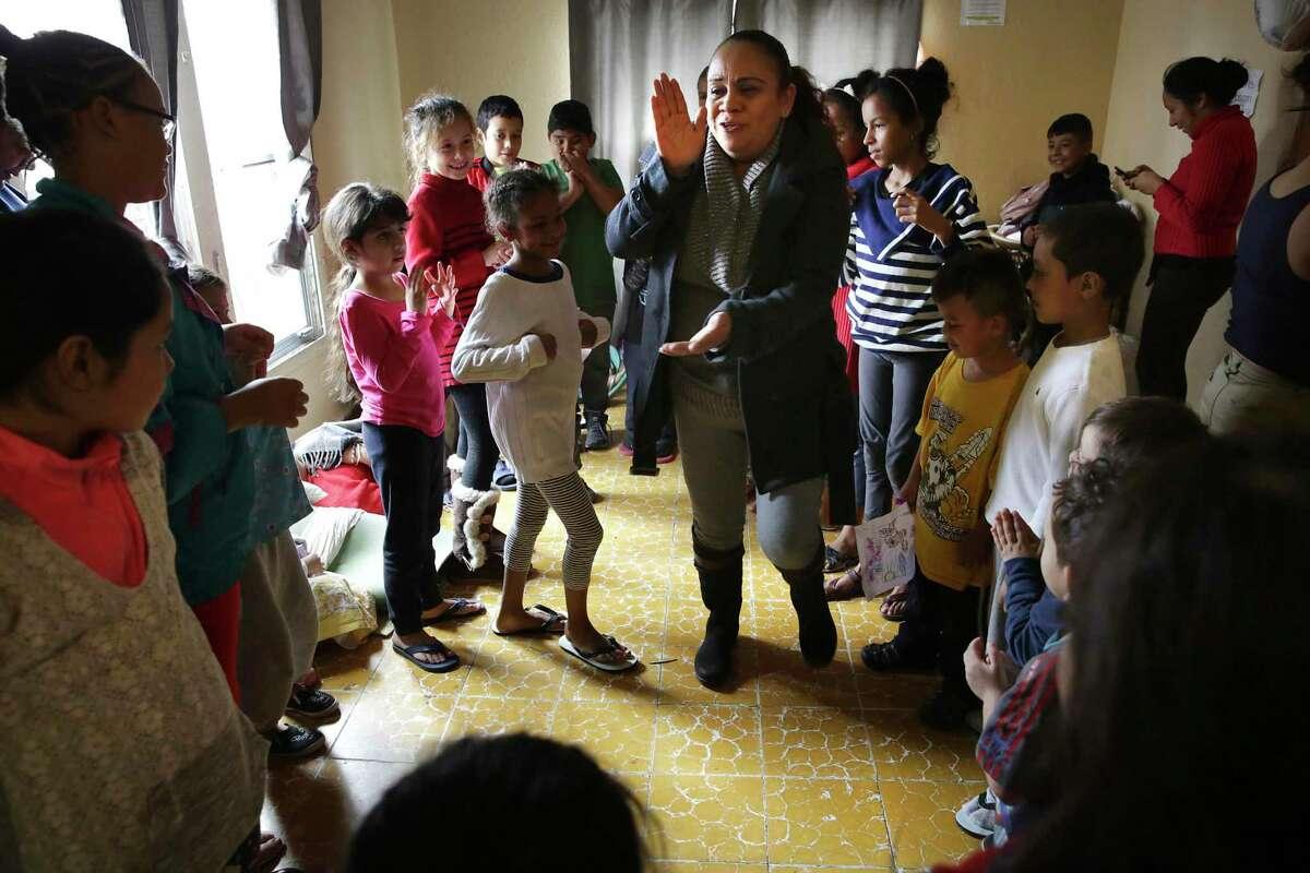 Miriam Maus, a youth pastor in Nuevo Laredo, leads asylum seeker's children in song and dance at Good Samaritan Shelter in Nuevo Laredo, MX on Wednesday, Nov. 13, 2019.