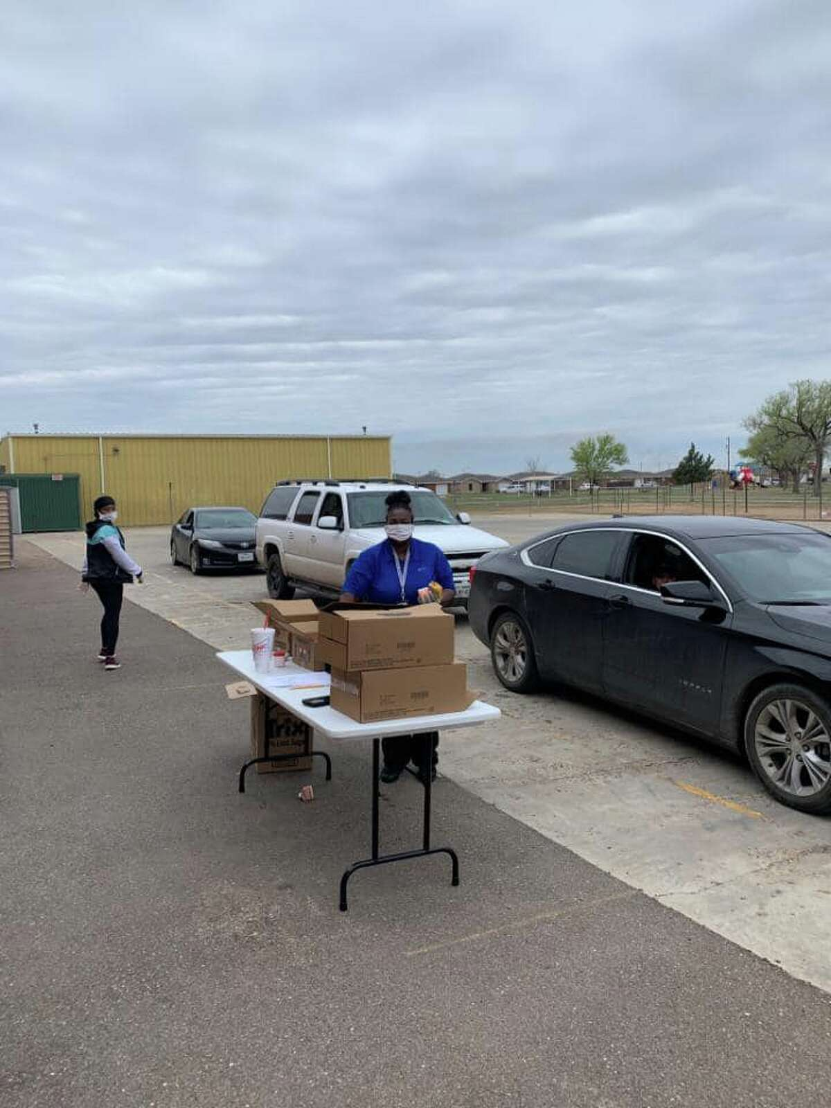 Plainview ISD volunteers provide curbside service to distribute meals to kids on Monday.