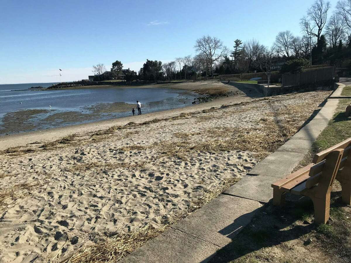 A parent and their child enjoy the relatively empty Compo Beach area late Tuesday afternoon. Taken March 24, 2020 in Westport, Conn.
