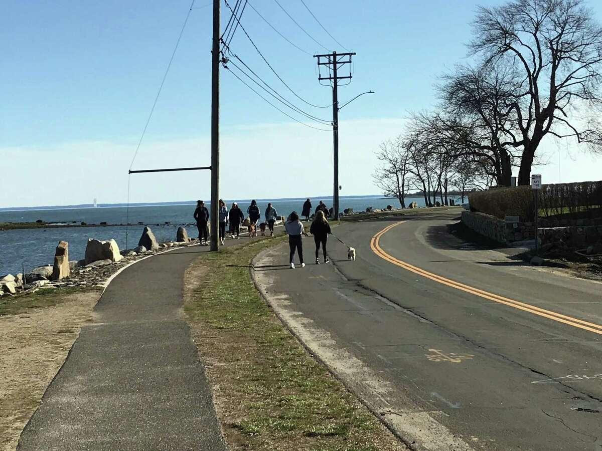 People walking alongside the Compo Beach area late Tuesday afternoon. The beach was not crowded despite the good weather. Taken March 24, 2020 in Westport, Conn.