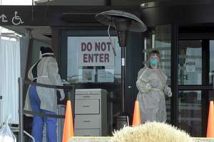 Stamford Hospital nurses wear protective gowns, gloves and masks in an area outside the hospital that has been set up to test for the COVID-19 virus in Stamford, Connecticut on March 17, 2020. Mobile testing of potential patients who may be suffering or have been exposed to the COVID-19 virus, the site is capable of testing up to 40 patients by appointment only and is one of several sites be established in the state in response to the Coronavirus pandemic.