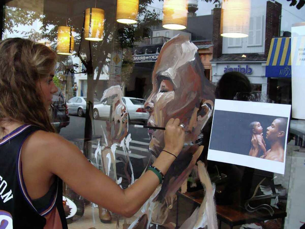 Carly Malpass, 17, of Darien, paints a father holding his infant on on a window in front of Shoe-Inn on Main Street in Westport. Malpass is one of 16 artists participating in a fund-raising art competition for Save the Children.