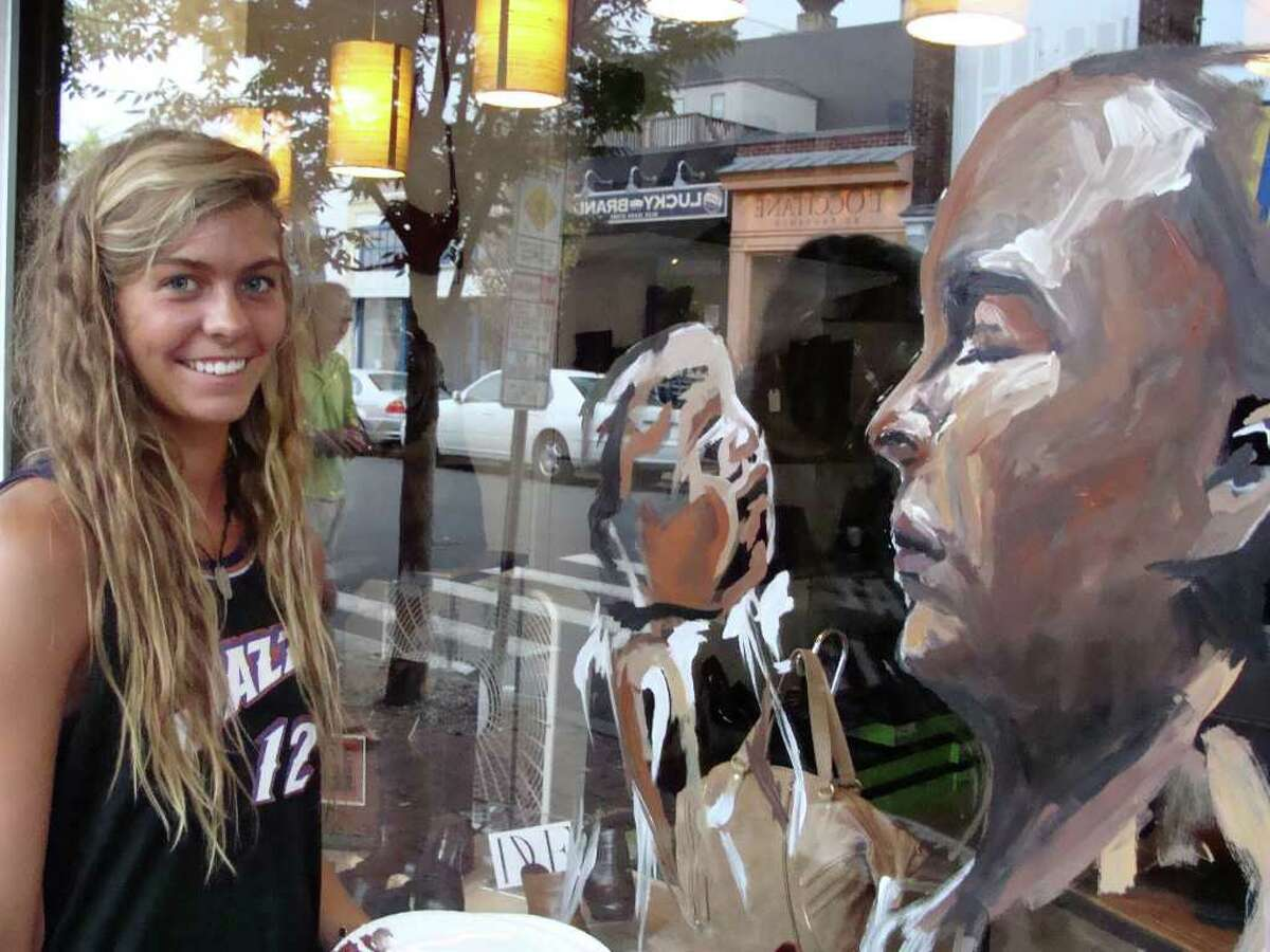 Charly Malpass, 17, of Darien, shows why she will study at the San Francisco Art Institute this fall. Malpass painted an elaborate portrait of a father holding his infant on the window od Shoe-Inn on Main Street as part of a Save the Children fund-raiser that will provide child-friendly space kits, including beach and sports balls, dolls and toys, to children affected by disasters close to home and around the world.