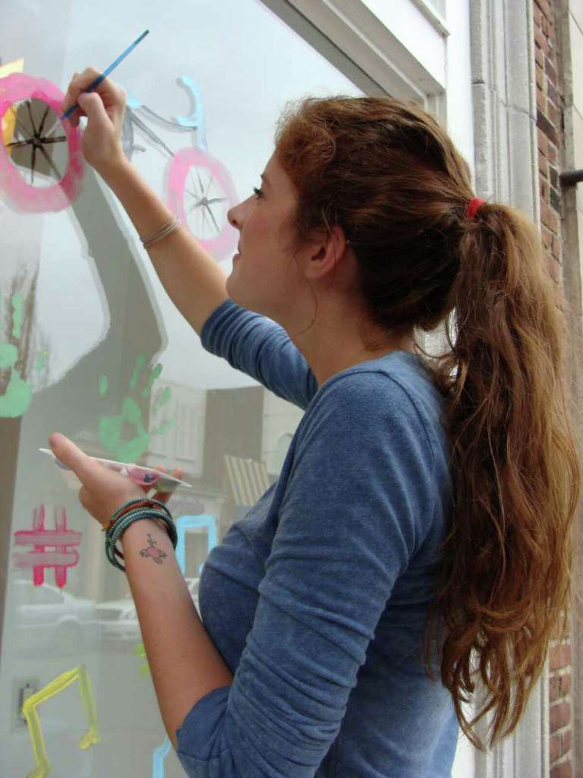 Skye Davis, 17, of Westport, works on a bicycle, part of a larger painting that she and friend Holly Stewart, 17, of Westport, created together for the Save the Children window art competition on the storefront of BCBG MaxAzria.