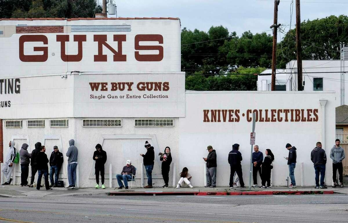 People wait in a line to enter a gun store in Culver City, Calif., March 15, 2020. (AP Photo/Ringo H.W. Chiu)