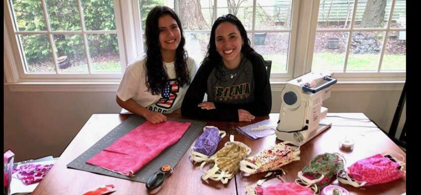 Siena lacrosse player Megan Power, right, and her sister, Grace, are making masks in their kitchen in Cranford, N.J. (Megan Power)