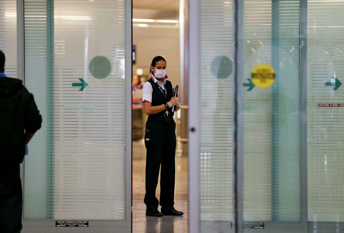 An airline employee wears a face mask amid fear of the new coronavirus in the international terminal at George Bush Intercontinental Airport on Thursday, March 12, 2020, in Houston.