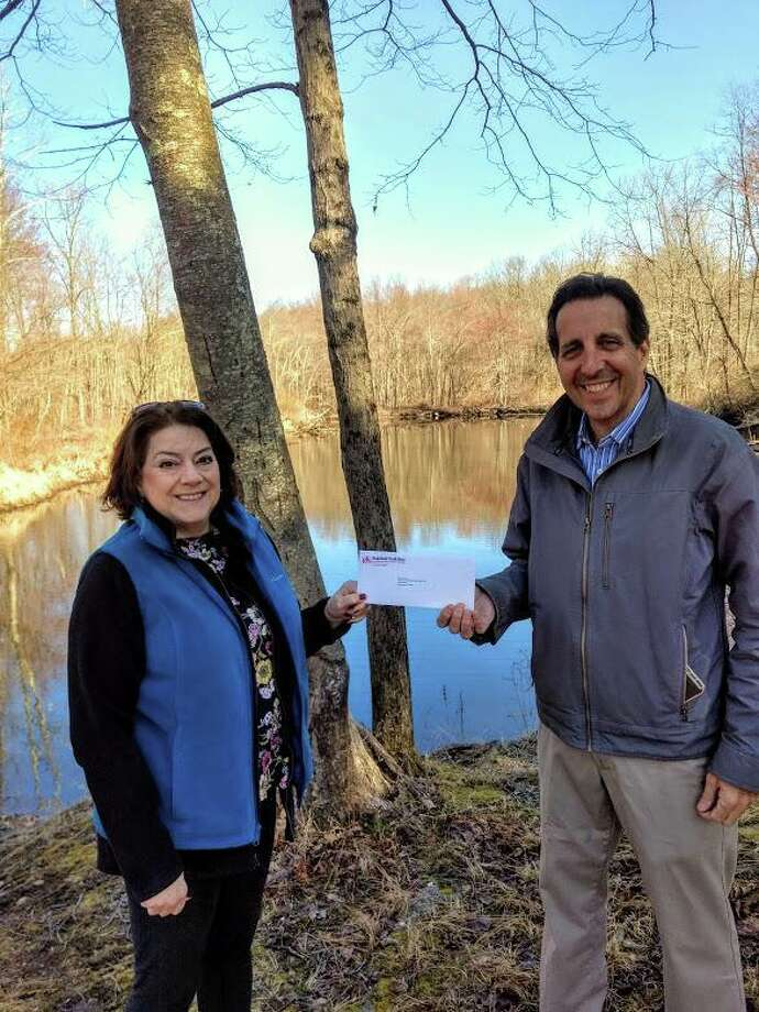 NRVT Executive Director Beth Merrill receives a check from Ridgefield Thrift Shop volunteer Alan Welby. Photo: Contributed Photo