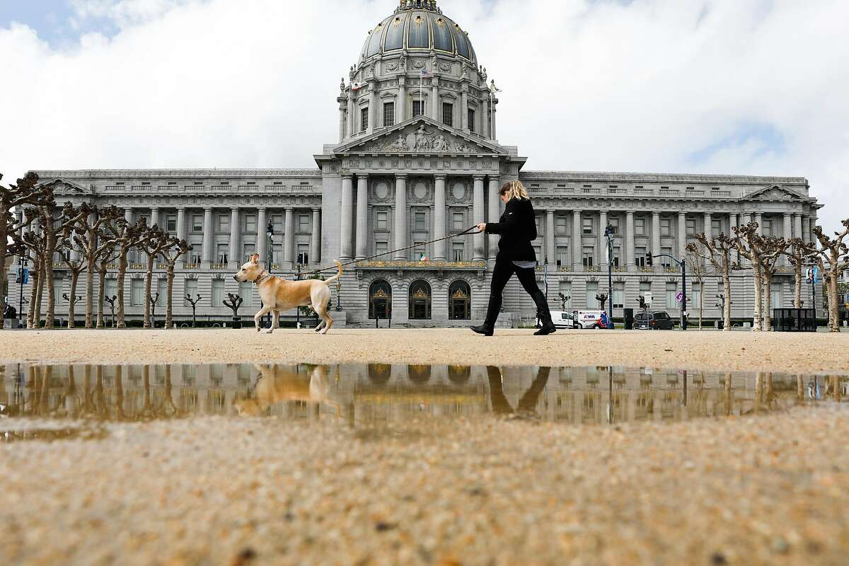 A woman walks a dog past City Hall on Sunday, March 15, 2020 in San Francisco, California.