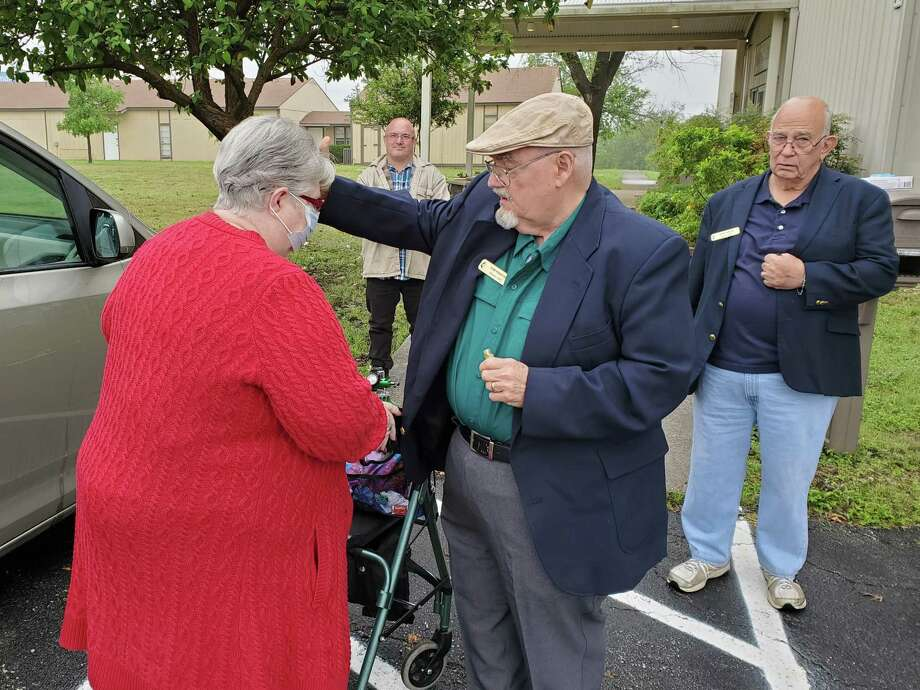 Alamo United Methodist Church pastor's assistant Tom Kinkead blesses and prays for church member Kathy Vedell Sunday during curbside service offered by the church on Foster Road near Kirby. Photo: Jeff B. Flinn / Staff