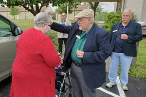 Alamo United Methodist Church pastor's assistant Tom Kinkead blesses and prays for church member Kathy Vedell Sunday during curbside service offered by the church on Foster Road near Kirby.